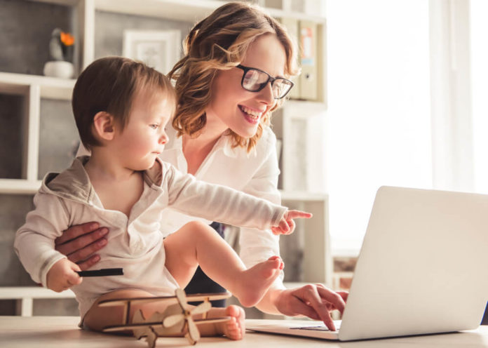 A woman is managing a business from home while taking care of her son